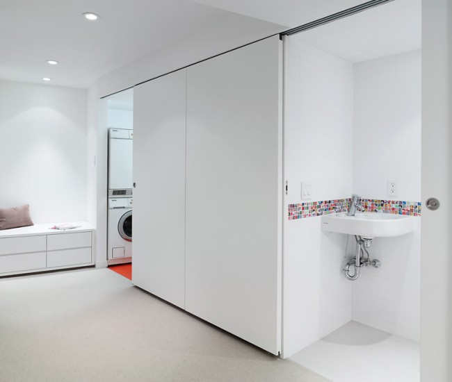 In the basement, laundry utilities and a powder room are concealed by lacquered wood doors by Gibson Greenwood.
