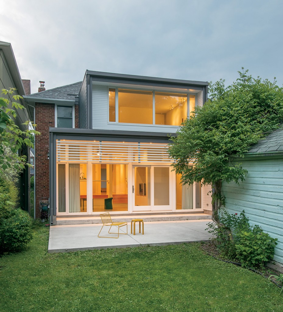 At the back, the addition and poured concrete patio– kept unpolished for traction– replace a deck. Wooden slats shade the glazed wall of the living room.