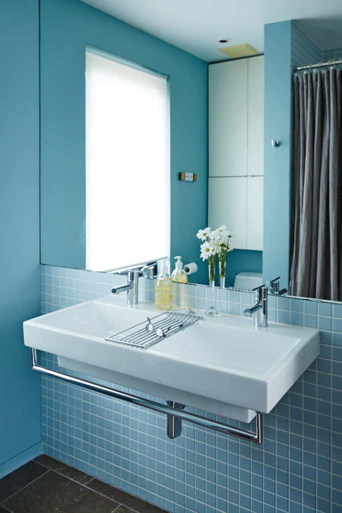 Architect/designer Andrew Jones updated the bathroom with powder-blue tiles and limestone flooring. The mirror opens at both sides, revealing his and her shelving.