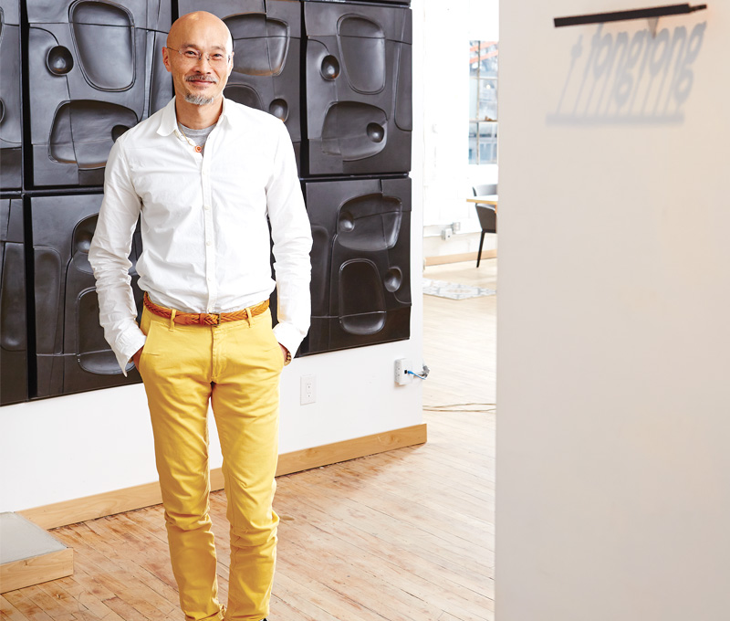 """John Tong stands in front of prototypes for the """"Mooncake"""" tabletop, inside his west end studio; wall-mounted, 3‑D-printed nameplate by Hot Pop Factory."""