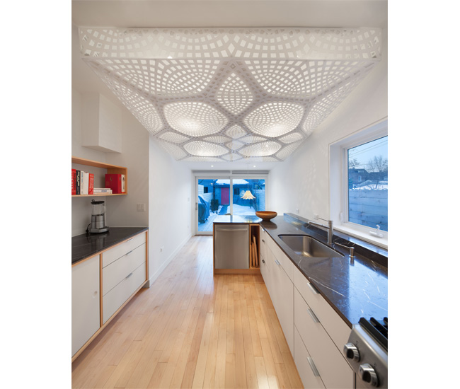 A laser-cut acrylic light box bridges a kitchen's high ceiling and a dinette's low roof. Photo by Alan Hamilton.