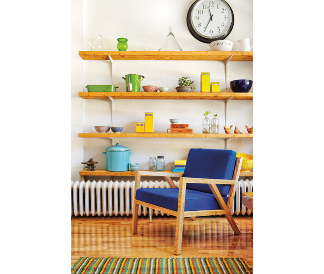 Scaffolding planks support a collection of vintage kitchenware and storage canisters. Truss chair by Gus Modern, rug from Pottery Barn and school clock from Ikea.