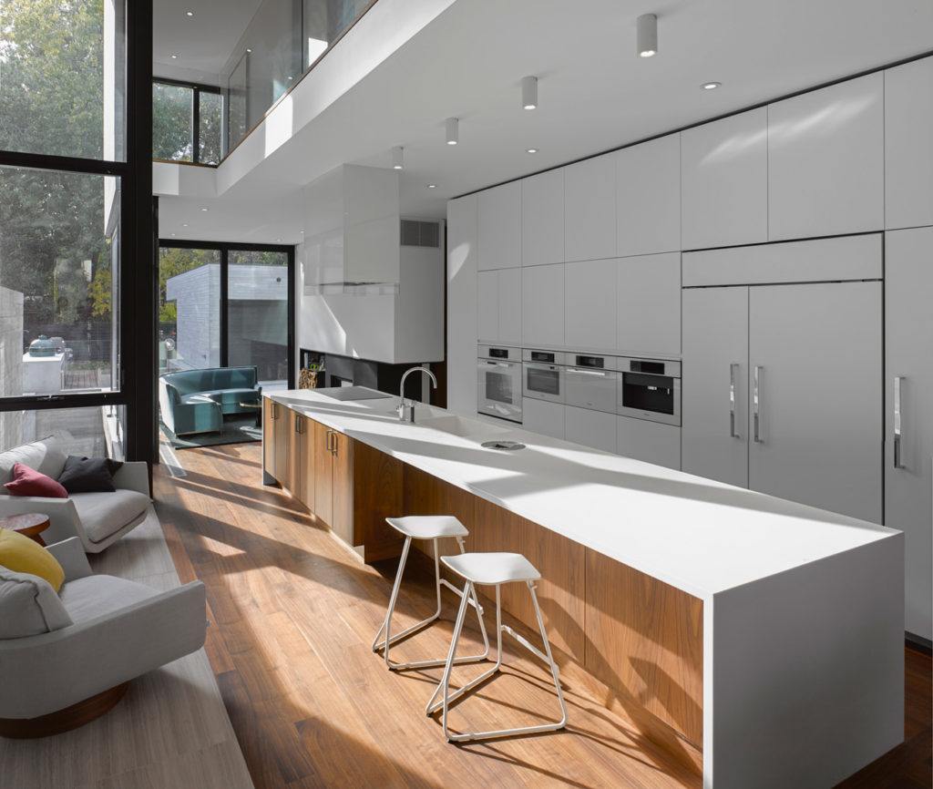 Walnut flooring and built-ins warm the cool interior. Lacquered cabinetry by O'Sullivan Millwork houses Miele's Brilliant White appliances; the five-metre-long island is topped in Corian. Photo by Ben Rahn/A-Frame.