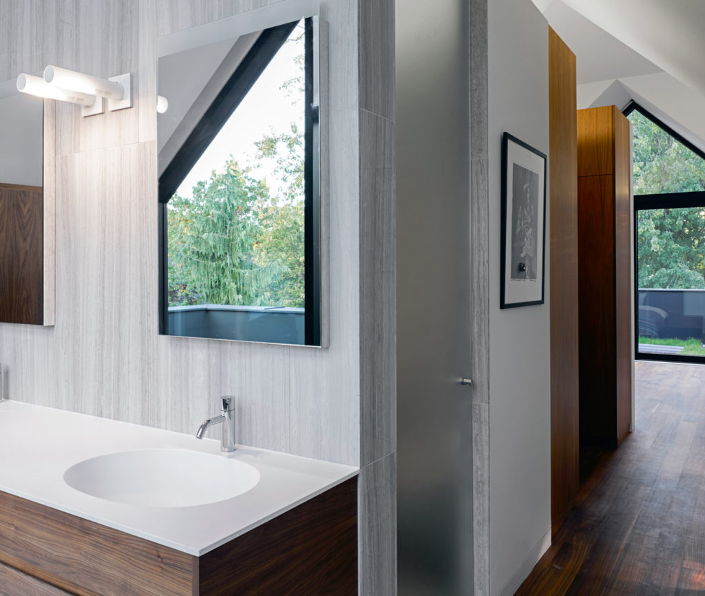 Partial walls in the open-concept master suite define bathing, dressing and sleeping spaces. Large-format limestone tile from Stone Tile. Photo by Ben Rahn/A-Frame.