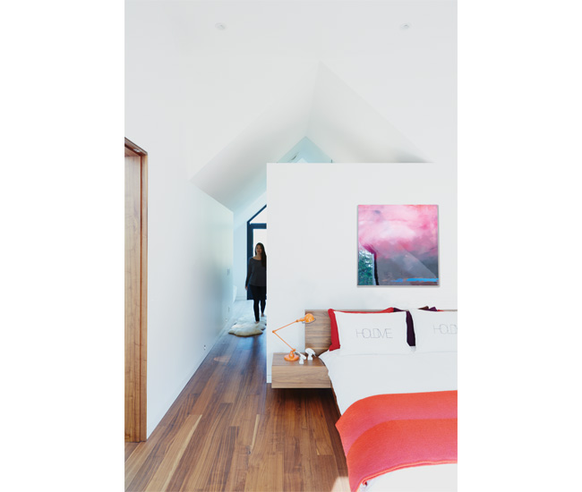 The peaked roof translates to a cathedral ceiling upstairs. Pillowcases from Made; lamp from Hollace Cluny; painting by Jay Hodgins from Art Interiors; bed from Urban Mode. Photo by Naomi Finlay.