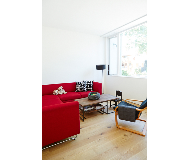 The living room's large windows overlook the neighbourhood. Sofa, lamp, pillows and throw from EQ3; armchair from IKEA; rubber-knit bowl from RADform.