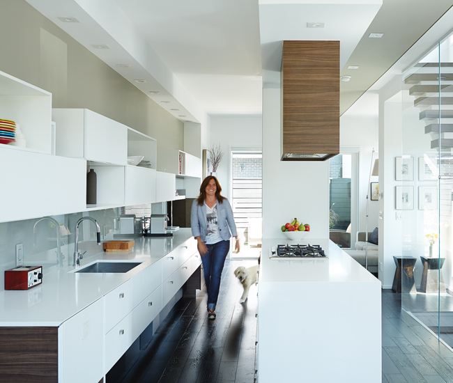 Jill and Pollie take a spin around the  Caesarstone-topped kitchen island anchoring the seamless ground level. The open-tread staircase filters south-facing sunshine. Flooring by Satin Finish Hardwood; kitchen by Cartier.
