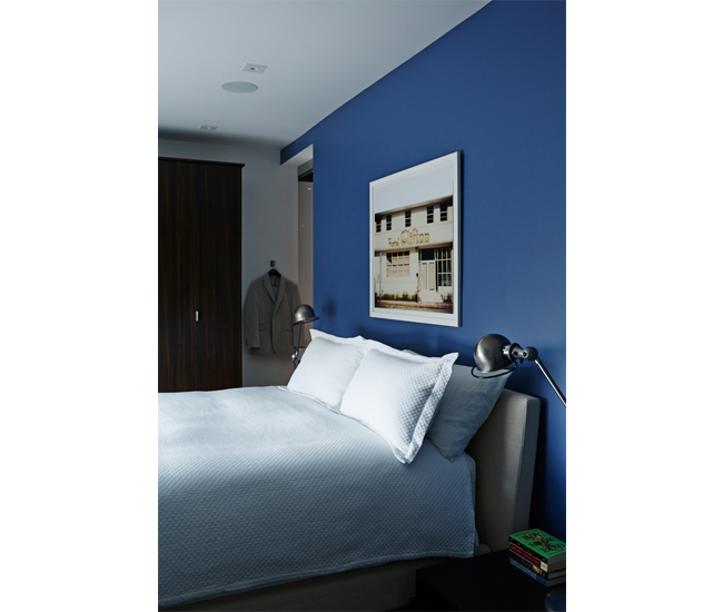 Rob had the second-storey master bedroom painted the Pantone shade of blue representing his birthday. Wardrobe by California Closets; Jieldé lamps available at Hollace Cluny; bed from DWR.