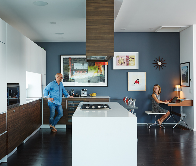 Over at Rob and Daryn's, the third-storey kitchen shares space with the living room. Here, cabinetry sandwiches an island/breakfast bar. Desk from Design Within Reach; photo by James Storie; prints by Gary Taxali and the Royal Art Lodge.