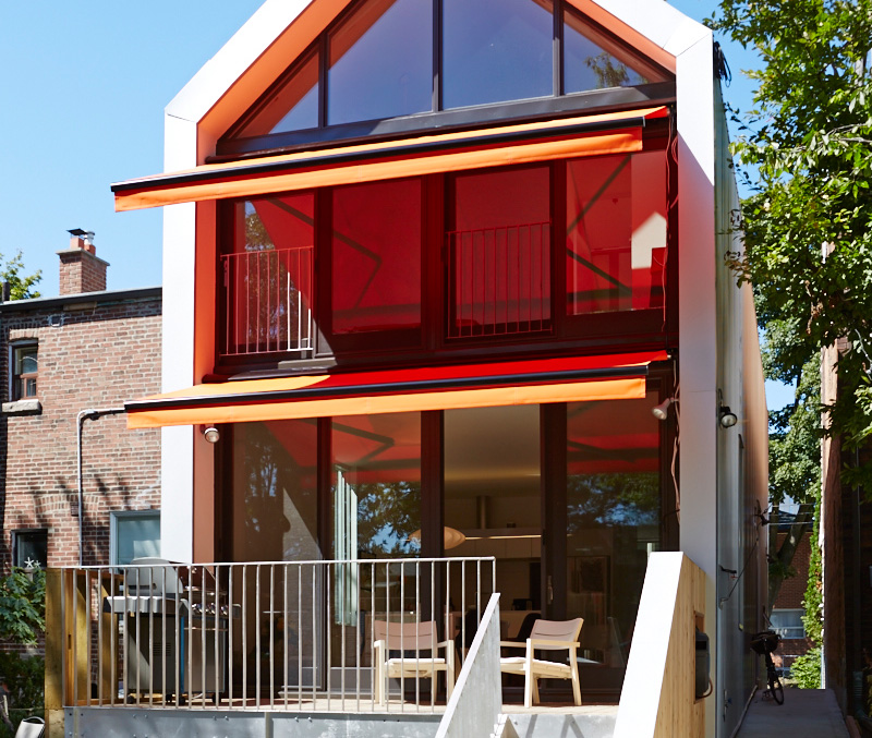 Retractable orange canopies from Rolltec shade the back of the house. A tiered rock garden leads to a lower patio and walk-out basement. Armchairs from Avenue Road.