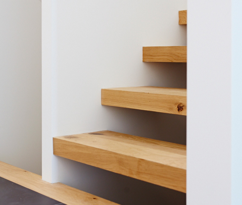 Sixty-five-millimetre–thick stair treads lead to the second storey and the basement. White oak engineered flooring throughout from Stone Tile.
