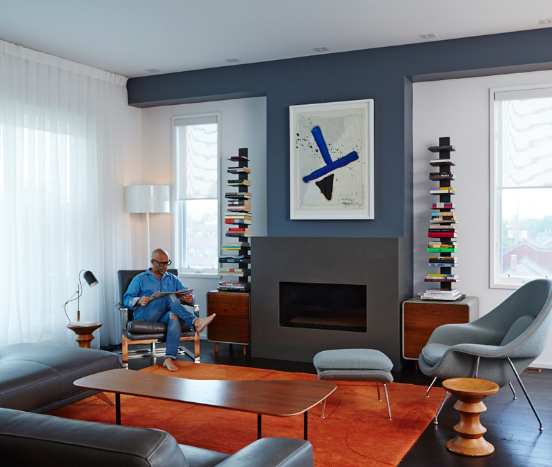 Across the way, in the third-floor living room, a Julian Schnabel resides over the fireplace. Wood/concrete cabinets from Made; rug, chair and floor lamps from DWR.