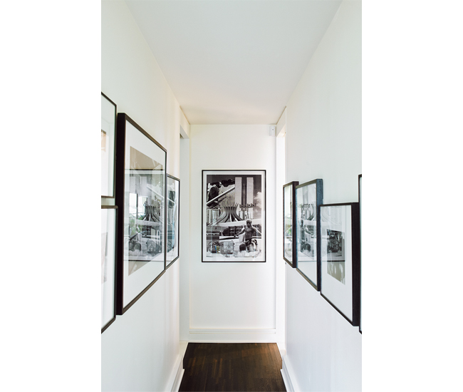 "The ""wedge"" hallway leading to the master bedroom doubles as a narrow photo gallery. Photo by John Cullen."