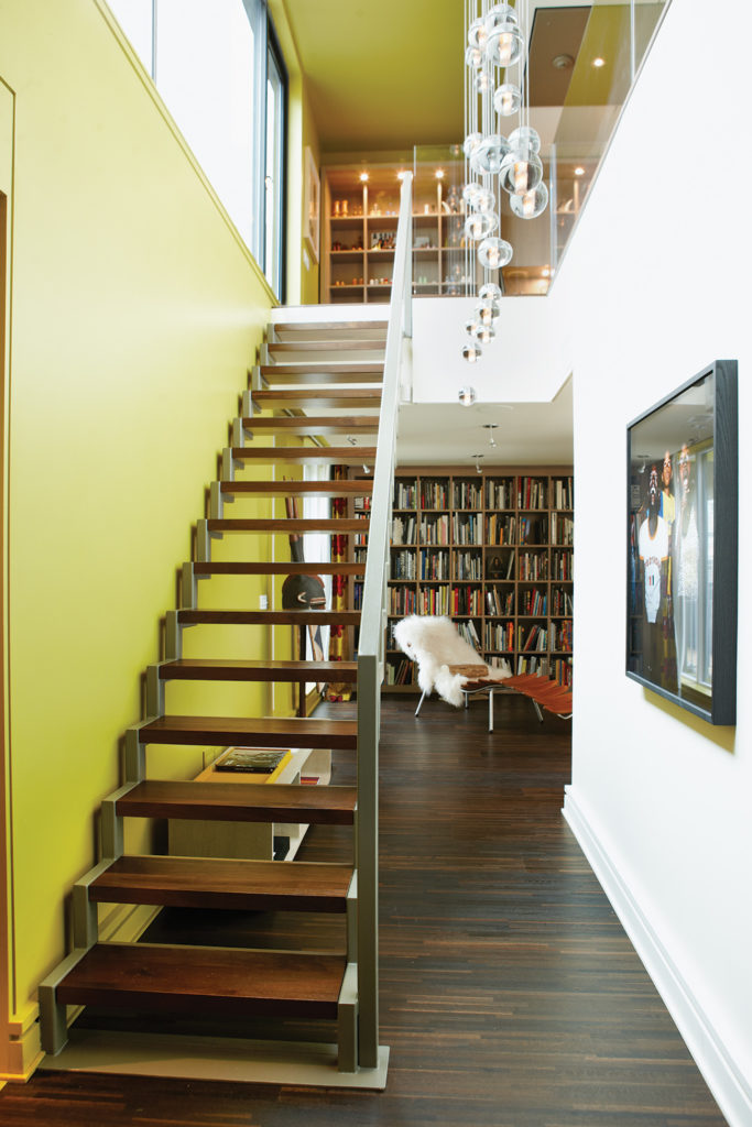A view of both storeys from the front door. The chartreuse wall matches the building's exterior. Bocci pendant lights by Omer Arbel. Photo by Naomi Finlay.