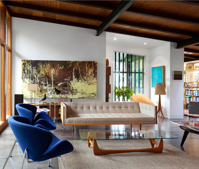 The house's slanted, tongue- and-groove ceiling and window frames are Spanish cedar. The table is by Eduard Kubis. Behind the Autobahn sofa is a painting by Brian Flanagan. Photo by Ben Rahn/A-Frame Studio.