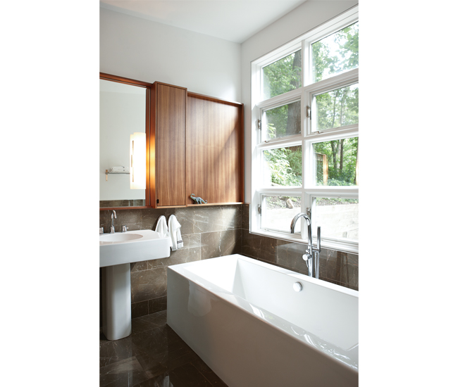 A wall of 12 industrial-style windows in the master bath face a tree-covered patio. Porcher sink and Flory de Colt soaker are from Tubs. Photo by Naomi Finlay.