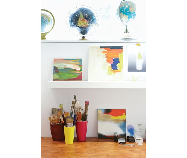 A bright painting studio has replaced a storage space downstairs. Among Kubis's canvases is a small portion of Martin's vintage globe collection. Photo by Naomi Finlay.