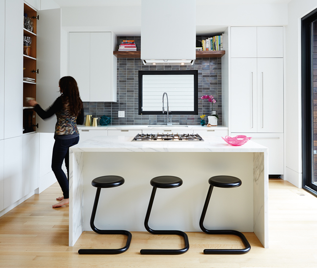Calacatta marble clads the kitchen's waterfall island. The backsplash's hand-made porcelain tiles are from Stone Tile.