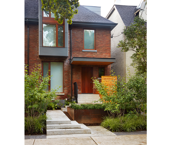 Cascading steps in polished concrete and neatly contained shrubs in a raised garden bed complement a Georgian's structural reinvention in Rosedale.