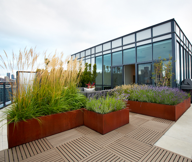 "A wraparound rooftop patio in Corktown was divided into ""rooms"" using stone tile flooring and Corten steel planters filled with quivering feather grass."
