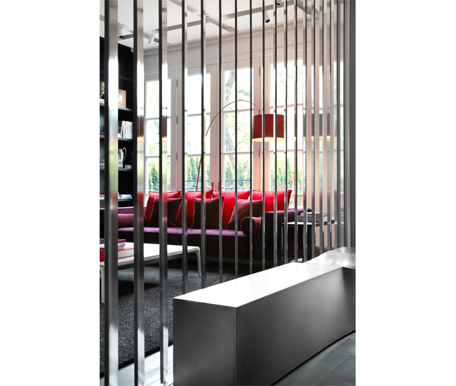 Steel slats by Mariani Metal, are set at 30 degrees and screen the sitting room from the entry. Sofa from Kiosk. Photo by Lisa Petrole.