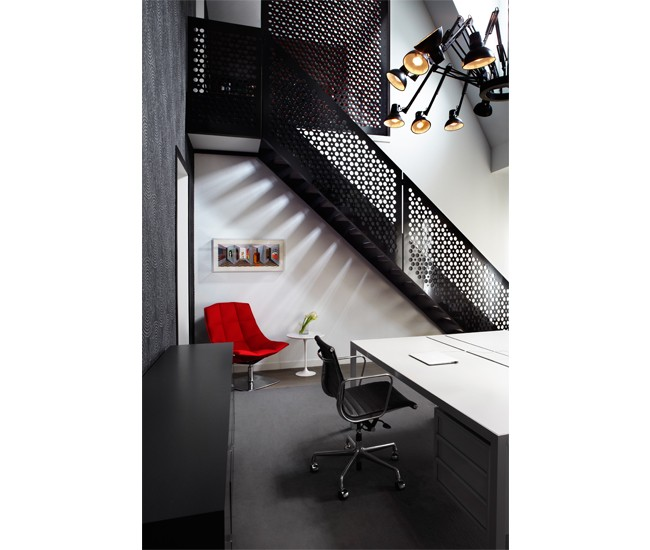 A custom staircase with red and black screens leads from the double-height office to a music room on the mezzanine. the walls are clad in sound- muffling object Carpet from are & be. moooi chandelier from Klaus. Photo by Lisa Petrole.