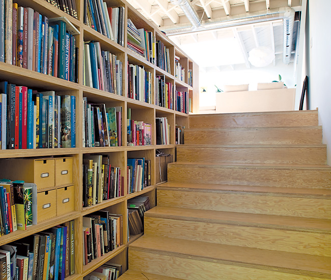 Monkman's book collection is hidden on shelves that continue around the corner and across the width of the upper space. The material here is doubled-up Douglas fir plywood.