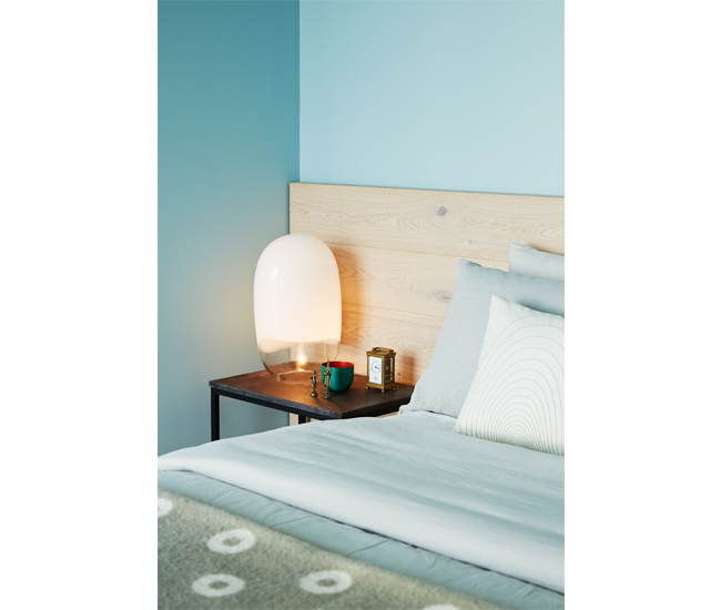 Surplus oak flooring was used to build a wall-to-wall headboard. The grey-blue picks up the wood's muted veining. Vintage Ghost lamp from Zig Zag; blanket by Pia Wallen.