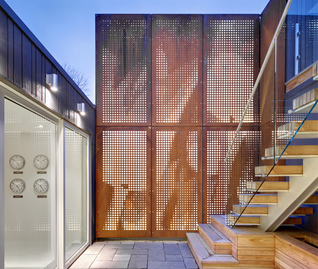 Backlit perforated Corten panels continue the facade's motif into the courtyard.