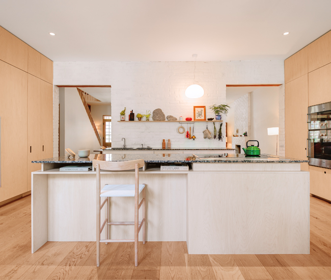The original rear exterior wall separates the living room from the new maple-clad kitchen. Millwork by Kevin Karst.