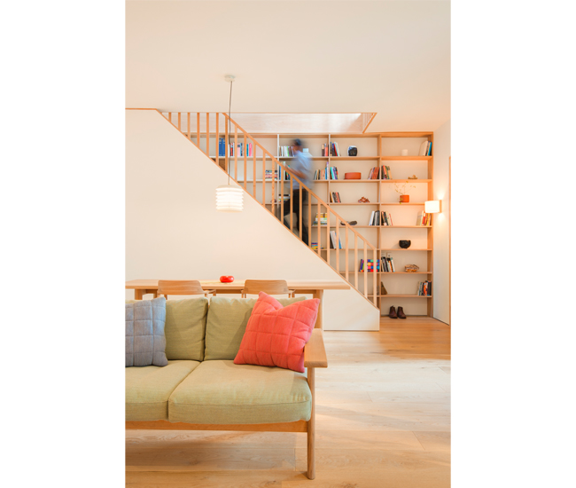 The oak stairwell is lined with a bookcase built by Trust Carpentry.