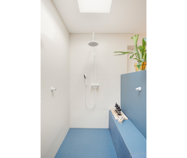 The bathroom's half-wall shields the shower. The raised surface of the tile (from Stone Tile) provides a slip-free surface.