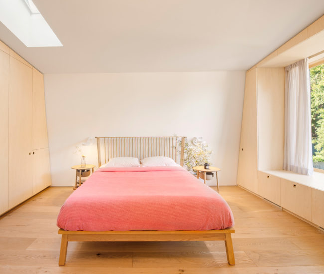 In the master bedroom a metre-wide windowseat overlooks the garden. Side tables and Ilse Crawford bedframe from Mjölk.