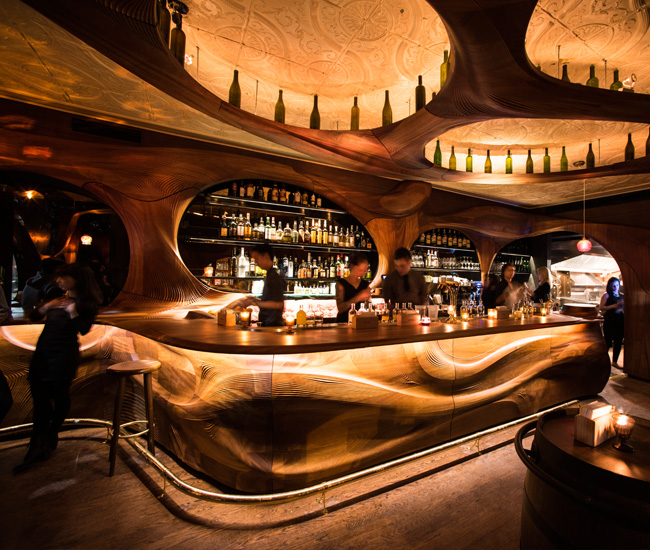 For Bar Raval, a pincho bar in Toronto's hip College St. neighbourhood, Partisans created an undulating sculpture of CNC'd mahogany that spreads across the ceiling and walls.