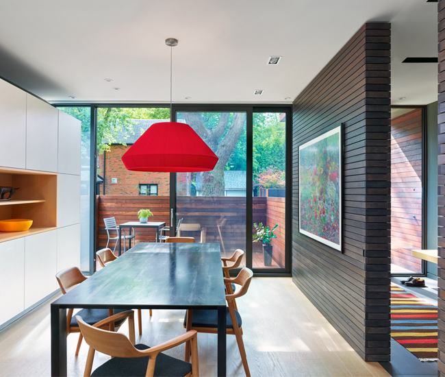 A grey-stained oak wall slides to close off the dining room from the adjacent foyer. Art by Christos Dikeakos; custom table by Commute Home; chairs from Mjölk.