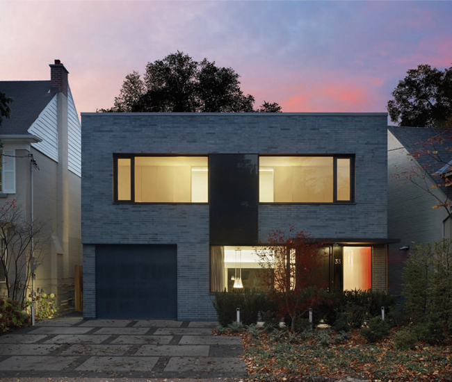 Unlike its more traditional neighbours, the new flat-roofed home sports such modern features as iron-spot brick and grey-tinted windows. Photo by Tom Arban.
