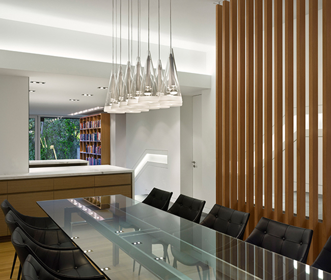 A vertical oak screen separates the dining room and foyer. Philippe Starck chairs from Italinteriors and Flos pendant from Quasi Modo. Photo by Tom Arban.