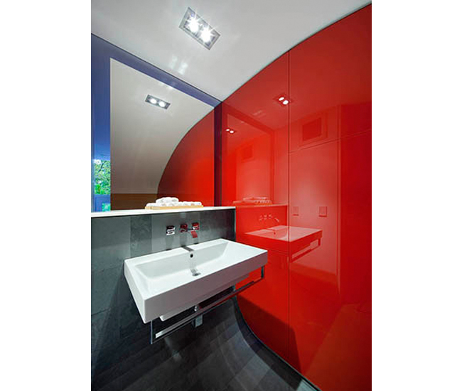 The first-floor wash- room is defined by a curved ceiling and floor, as well as a red wall. Clear glass surrounding the mirror provides a peek outside. Photo by Tom Arban.