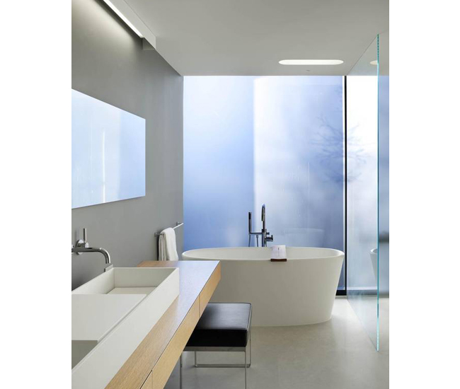 Low-iron glass partitions separate the master bath from the bedroom. Tub by WetStyle.