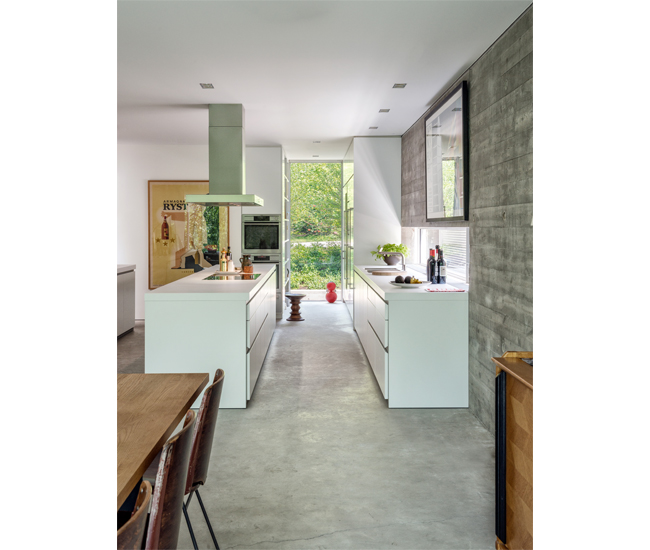 Long and narrow windows keep the kitchen airy, as does the lack of uppers. Deep units by Bulthaup, as well as a pantry, make them unnecessary. Prints hang from an ingenious aluminum track recessed into the concrete wall. Photo by Bob Gundu.