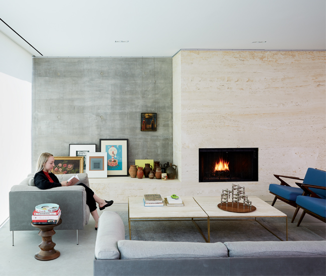 A honed travertine-encased Heatilator fireplace warms up the cool, board-formed concrete walls. Photo by Naomi Finlay.