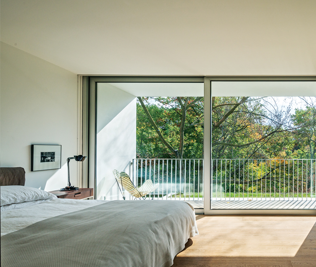 A glazed wall by Door Studio in the master opens up to the second storey–long balcony. Bed from Palazzetti. Photo by Bob Gundu.