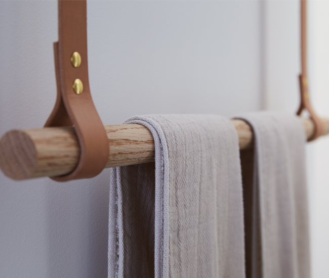 Another ingenious custom flourish: an oak dowel towel rack, hung on ceiling-mounted, tanned leather straps. Photo by Naomi Finlay.