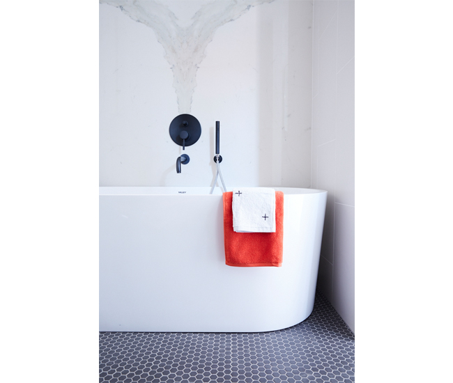 An oval soaker tub by Valley pops against Stone Tile flooring and Ciot wall tile. Towels from CB2 and Drake General Store. Photo by Naomi Finlay.