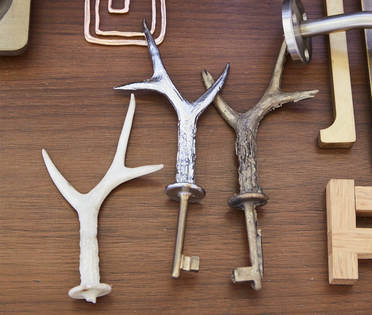 Cast bronze keys sit among custom hinges and handles.