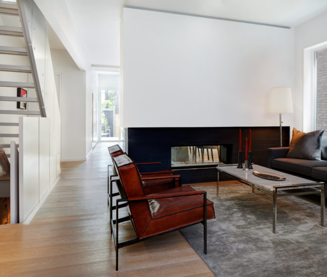 Ducts and electrical are tucked in the wall above the two-sided fireplace between living room and kitchen. Chairs from Hardware Interiors; rug and sofa from Elte.