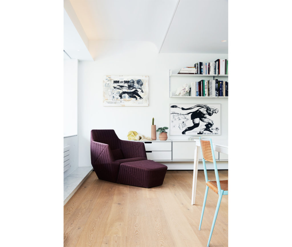 Paintings by WK Interact hang above Vitsoe Universal Shelving. Ligne Roset armchair at Kiosk. Photo by Naomi Finlay.