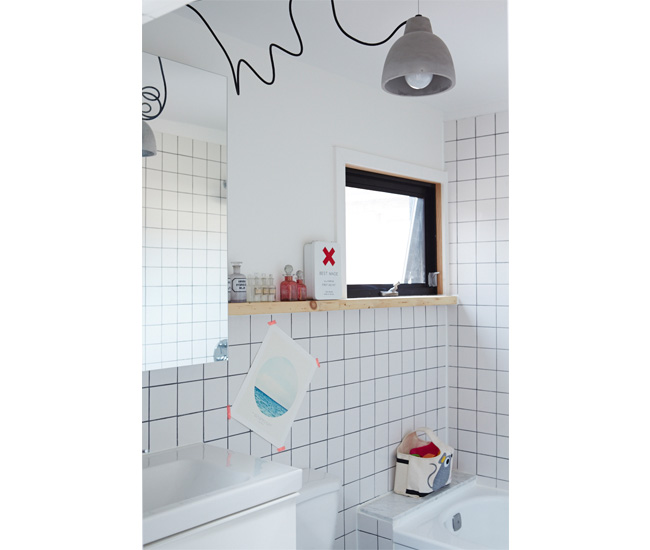 3 Go graphic. Hardware-store tile and black grout is installed graphic effect. Pendant, Home Depot; medicine cabinet, IKEA; window by Delta. Photo by Naomi Finlay.