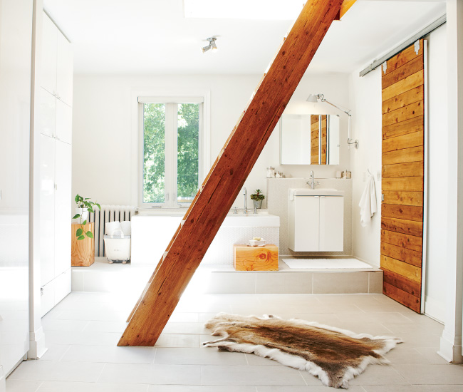 7 Use barn wood to introduce some cabin-style coziness. A pocket door in the master bathroom hides a water closet while the ladder leads to a rooftop patio. Ceramic tile from Olympia, tub by Neptune. Photo by Naomi Finlay.