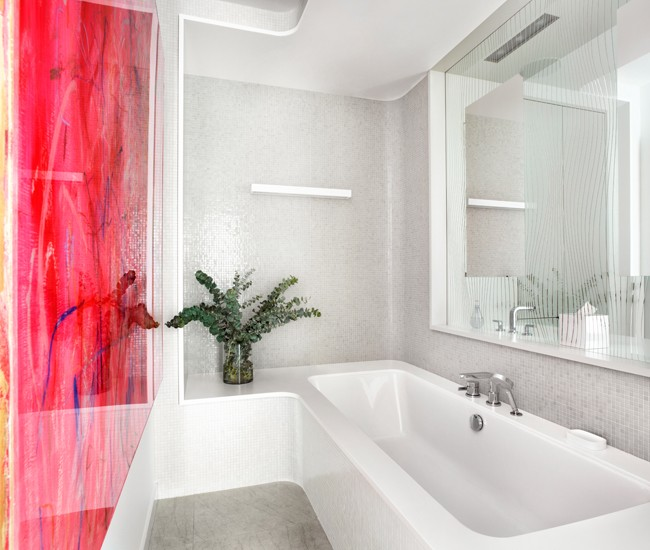 8 Separate bathing and washing spaces with an unconventional room divider. From the bathtub, you can see through the mirror (with its strategically removed silver) to the vanity next door. Art by Thrush Holmes. Photo by Lisa Petrole.